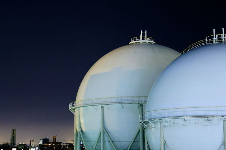 Low Angle View Of Gas Tanks In Industry Against Sky At Night