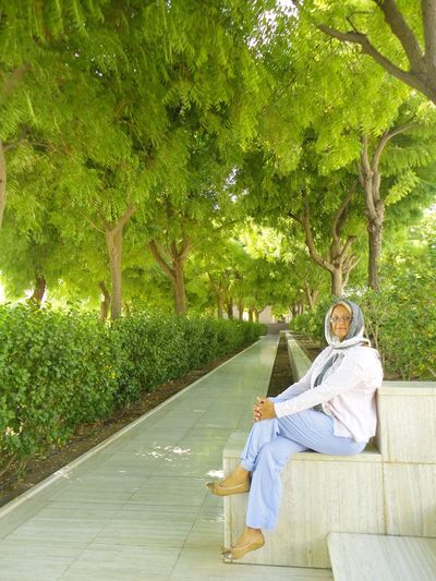 Portrait of senior woman sitting by footpath against trees