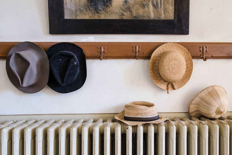 Wall hanger with various hats on it, radiator and old painting Classic EyeEmNewHere Wall Day Hangers Hats Indoors  No People Old Painting Radiator Straw Hat Tropical Hat Vintage Wall Hangers Wardrobe