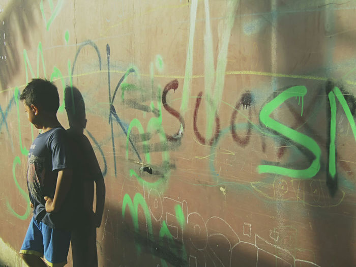 Full length of teenage boy with graffiti in city