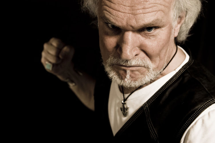 Portrait of angry senior man with clenching fist against black background