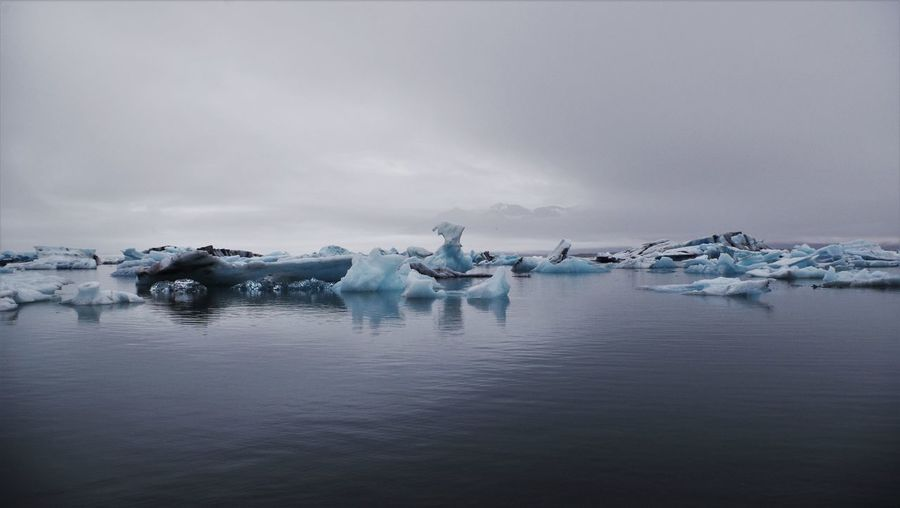 Scenic view of jokulsarlon with iceberg against cloudy sky