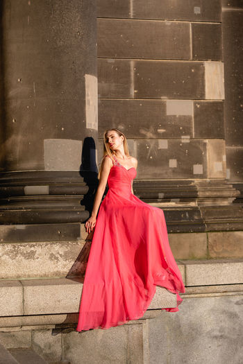 Full Length Of Woman Wearing Red Evening Gown Sitting On Steps