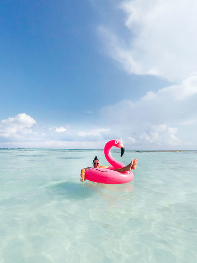 Young woman floating in inflatable ring on sea against sky