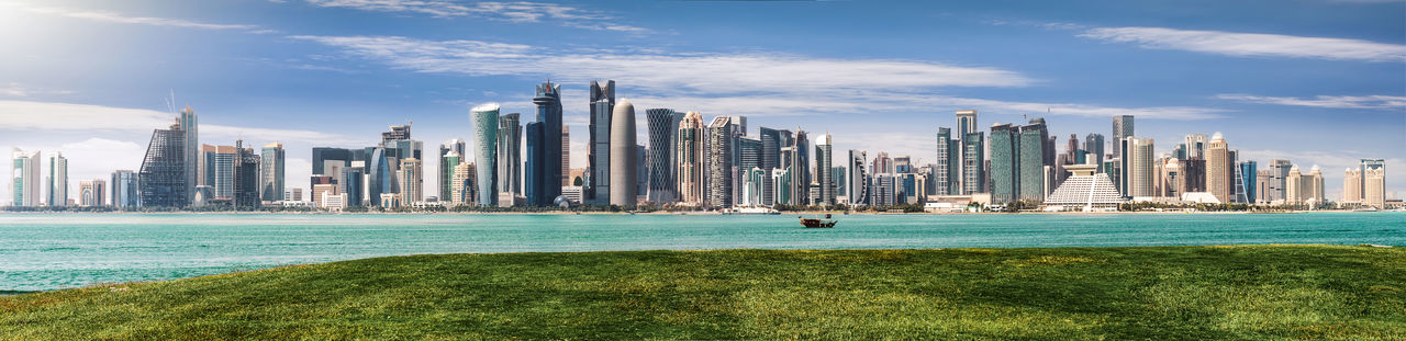 The modern skyline of Doha, Qatar, during a sunny spring day Arabian Architecture City Cityscape Doha Green Middle East Modern Skyline Tourist Attraction  Travel View Blue Corniche Day Mia Park Qatar Sky Skyscraper Spring Sun Tourism Travel Destinations Urban