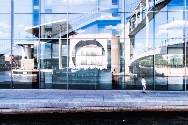 Reflection Of Bridge And Canal On Glass Building