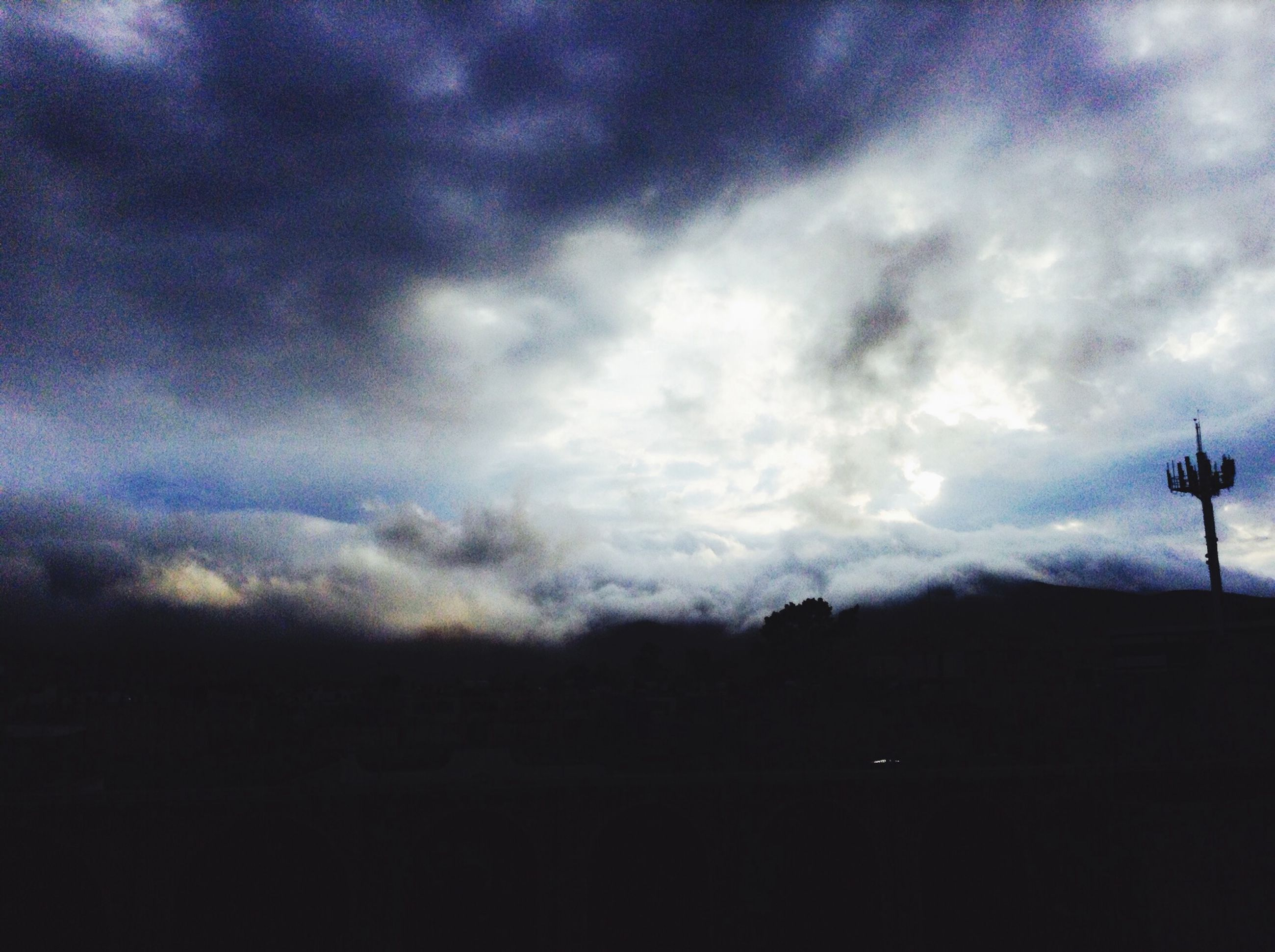sky, silhouette, cloud - sky, cloudy, tranquility, tranquil scene, scenics, beauty in nature, weather, dusk, nature, landscape, cloud, overcast, low angle view, mountain, outdoors, storm cloud, idyllic, dark