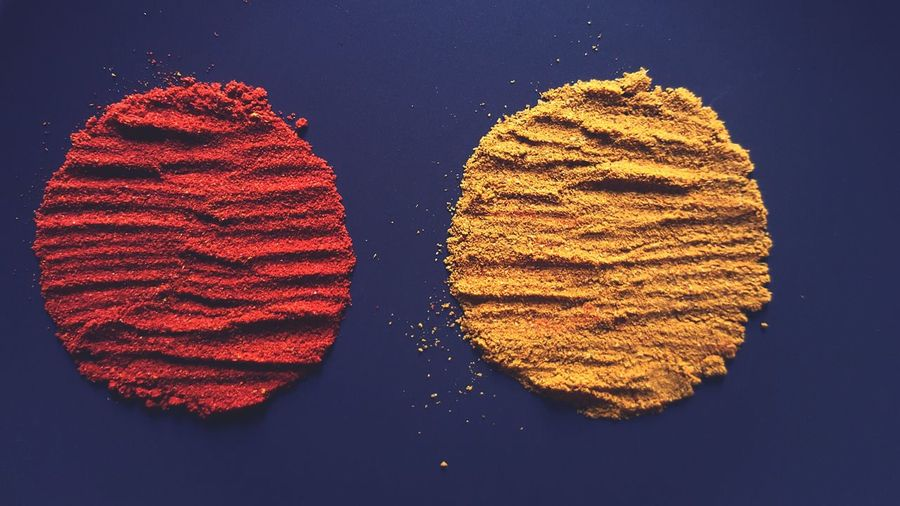 Close-up of paprika and cumin on blue background