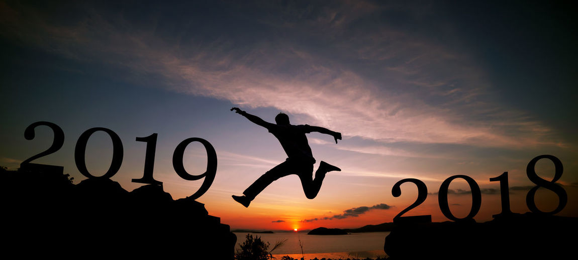 Silhouette man jumping by numbers against sky during sunset