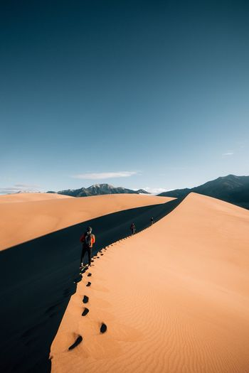Wander. Land Landscape Desert Sky Nature Arid Climate Climate Real People Sand Dune Adult Travel One Person Beauty In Nature FootPrint Sand Tranquil Scene Blue