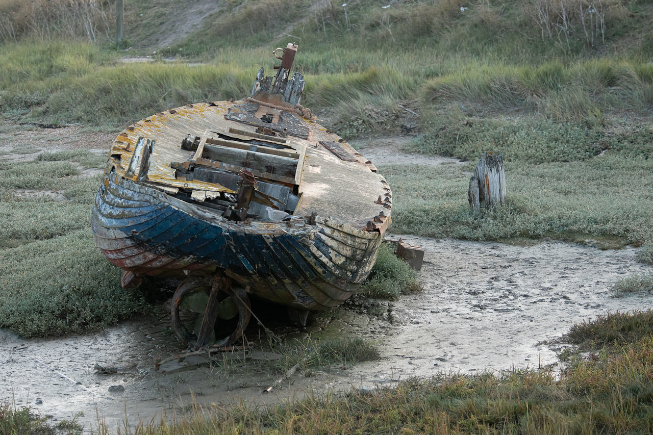 ABANDONED BOAT ON LAND IN GRASS