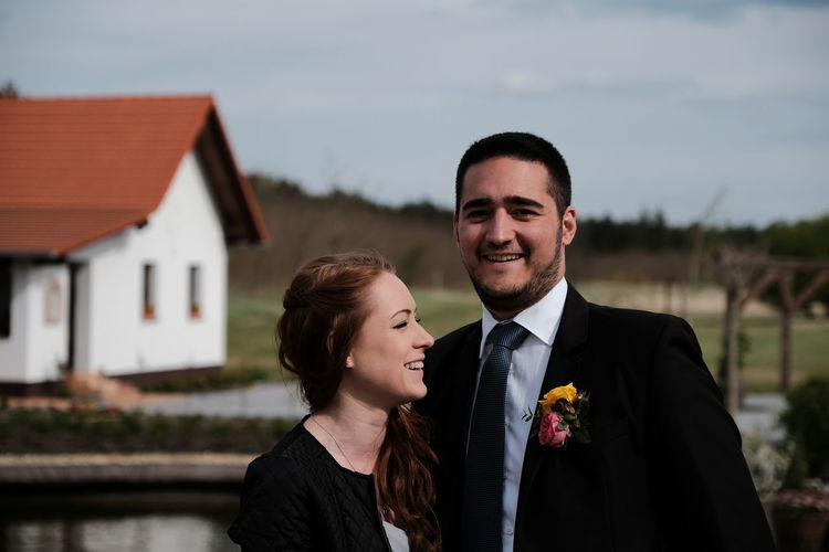 Smiling couple standing against house