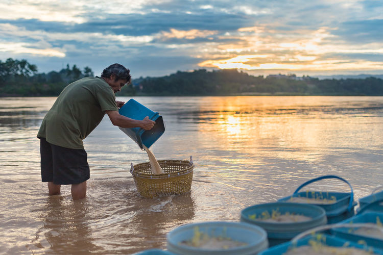 Side view of man pouring water in basket in lake during sunset