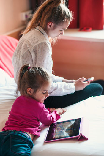 Sisters using technologies on bed at home