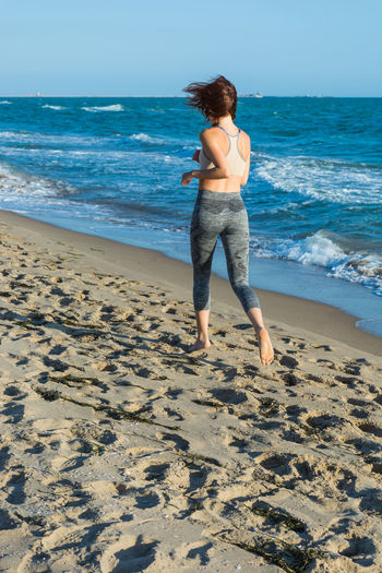 Rear View Of Young Woman Running At Beach