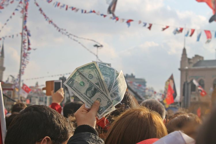 People holding paper currency in city against sky
