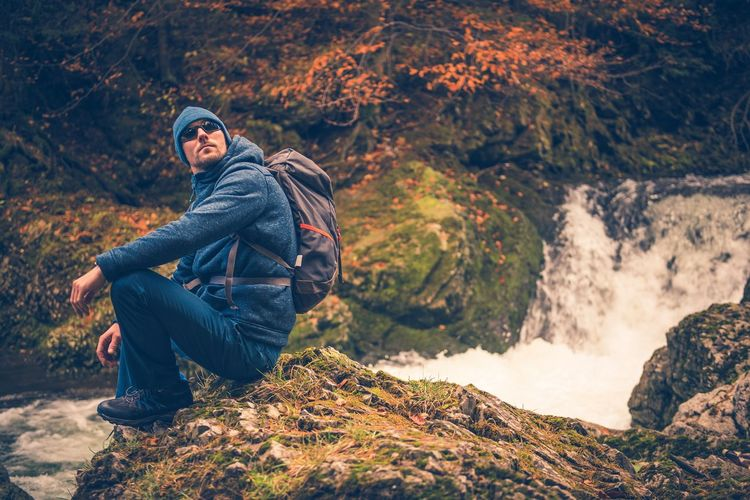 Side view of mid adult man with backpack sitting on mountain by waterfall