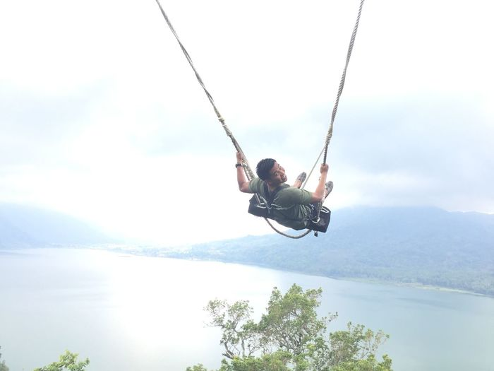 Man jumping on swing against sky