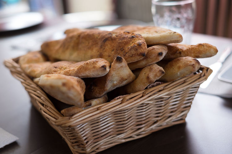 Close-up of baked breads in basket on table