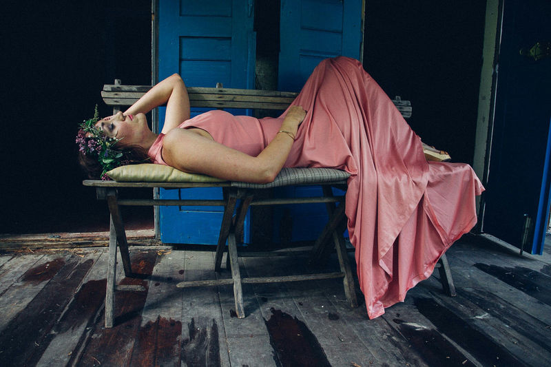 Young woman wearing peach gown while lying on bench at old house