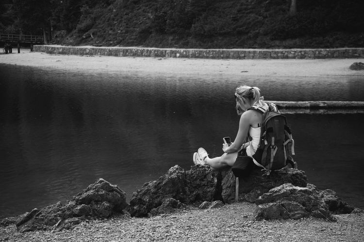 Rear view of woman photographing from mobile phone while sitting on rocks at lakeshore