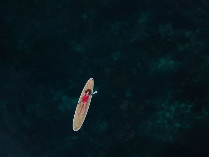Aerial view of woman lying on paddleboard over sea