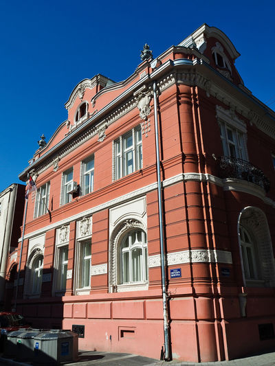 European Cities Novi Sad Serbia Balkans Europe Eastern Europe Outdoors Clear Blue Sky Architecture Facades Building Exterior Built Structure Low Angle View City Building Heritage Building Historical Place Painted Buildings The Past Sky Window No People Residential District Red Arch Street Corner