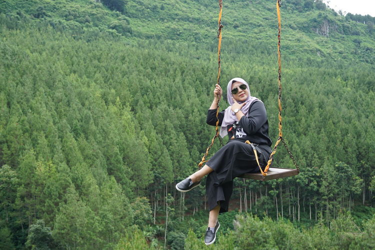 Full Length Portrait Of Woman Sitting On Rope Swing In Forest