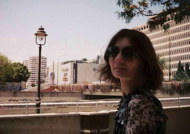 Portrait of woman wearing sunglasses in city against sky