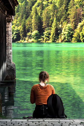 Rear view of woman sitting at lake against trees
