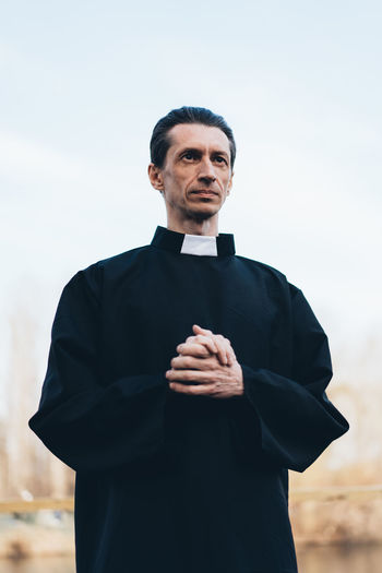Handsome catholic priest portrait with collar Pastor Priest Collar Religion Religious  Belief Saint Father Beliver Man Men People person One Person Caucasian Middle Ages Catholicism Catholic Christianity Christian Faith Standing Front View Males  Waist Up Real People Clothing Sky Focus On Foreground Day Lifestyles Black Color Mature Adult Portrait Mid Adult Men Looking At Camera Outdoors