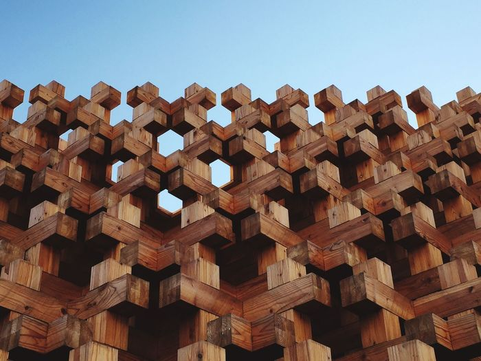 Low Angle View Of Wooden Sculpture Against Clear Blue Sky