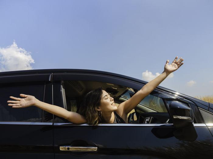 Woman sitting in car against sky