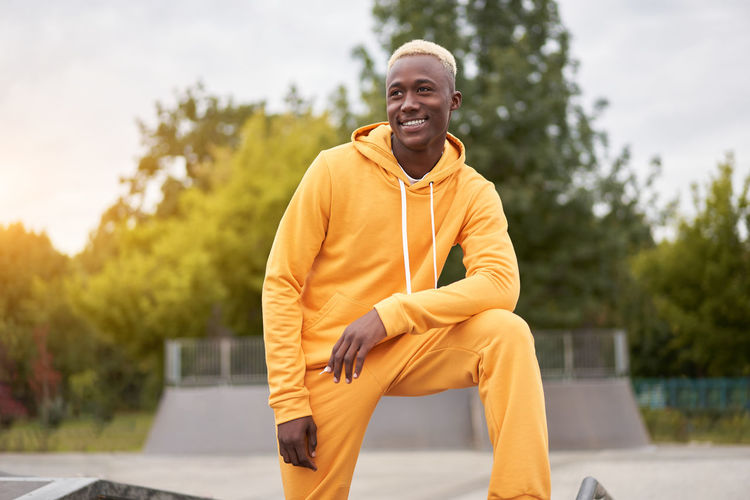 Smiling man looking away while standing in park