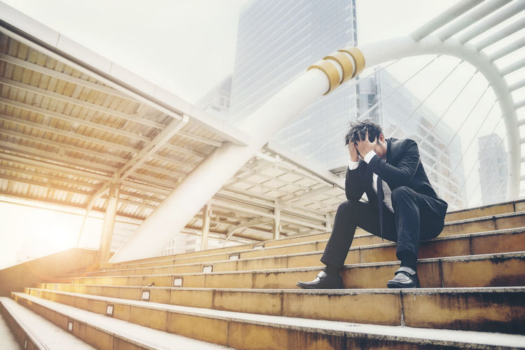 Full length of stressed businessman sitting on staircase in city