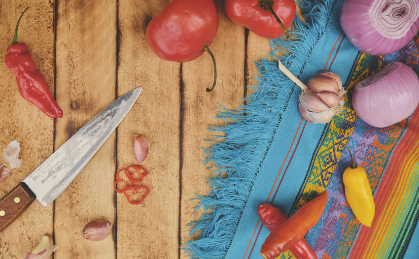 High angle view of hand holding vegetables on table