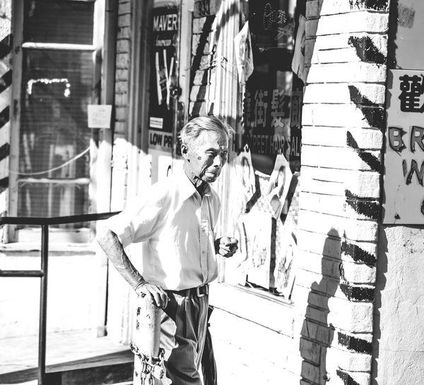 Man standing against graffiti in city