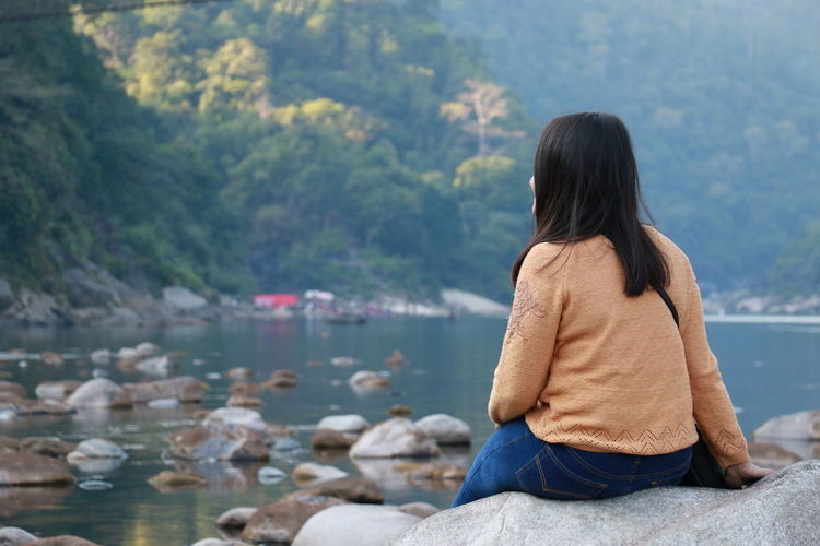 Rear view of woman sitting on rock while looking at sea