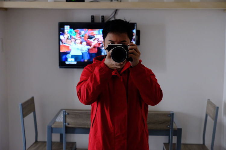Man Photographing With Camera While Standing At Home