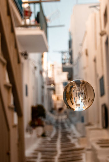 Low angle view of electric lamp on street by buildings