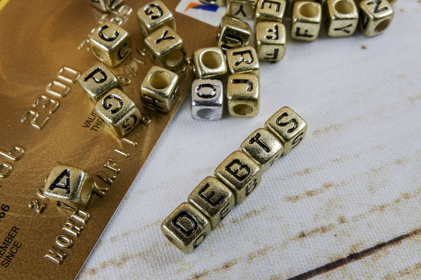 DEBT CONCEPT WITH GOLD DICE ON A WOODEN TABLE Close-up Communication Credit Card Currency Day Debt Crisis Equipment Finance Group High Angle View Indoors  Large Group Of Objects Metal No People Number Still Life Table Technology Text Textile Wealth Western Script