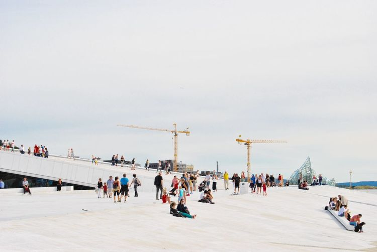 People At Oslo Opera House Against Clear Sky