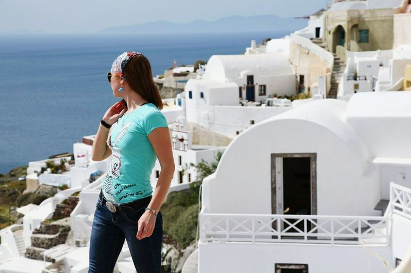 Woman Standing Against View Of Santorini