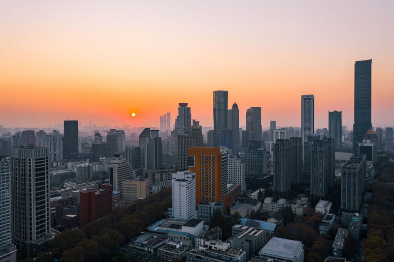 Aerial view of modern buildings against sky during sunset