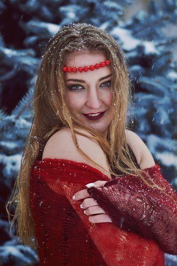 Portrait of beautiful woman standing in snowfall