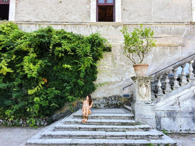 A portrait of a woman sitting on the steps of a baroque style building Architecture Baroque Architecture Building Built Structure Casual Clothing Day Full Length Green Color Green Wall Growth Hidden Gems  Historical Building Historical Sights Leisure Activity Lifestyles Outdoors Plant Sitting Stairs Steps Street Photography Travel Photography Urban Lifestyle Villa D'Este Young Women