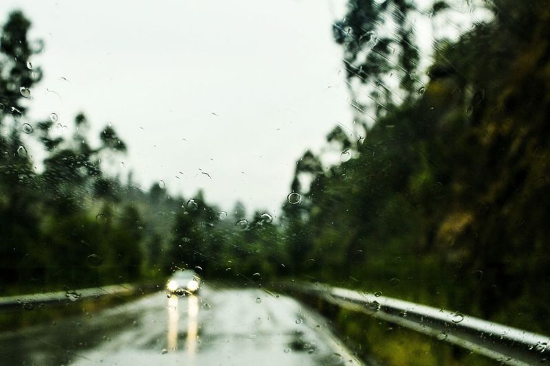 View of wet road against sky during monsoon