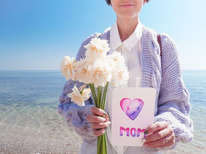 Young woman holding flower bouquet against sea