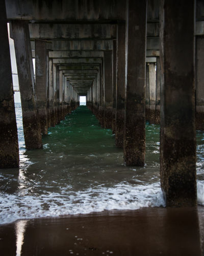 Under the Coney Island Pier in Brooklyn New York City. The perfect getaway from the population on the beach. Tranquil and calm. Architectural Column Architecture Below Bridge Built Structure Day Diminishing Perspective In A Row Motion Nature No People Outdoors Pier Reflection Sea Underneath Water