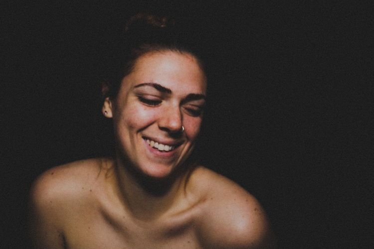 Smiling topless young woman against black background